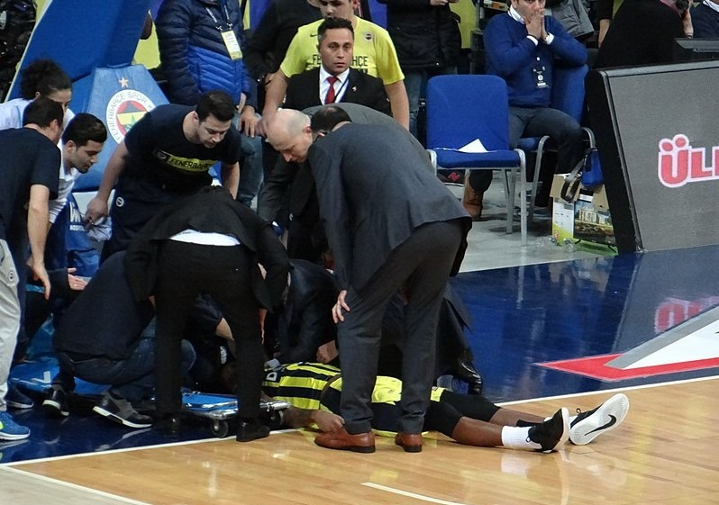 injured basketball player lying on the floor as people examines him