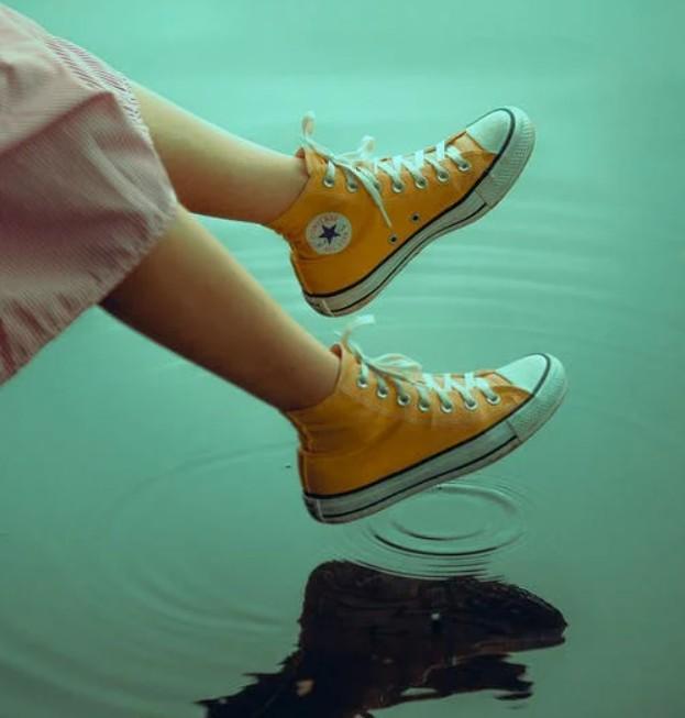 Girl wearing yellow Converse shoes